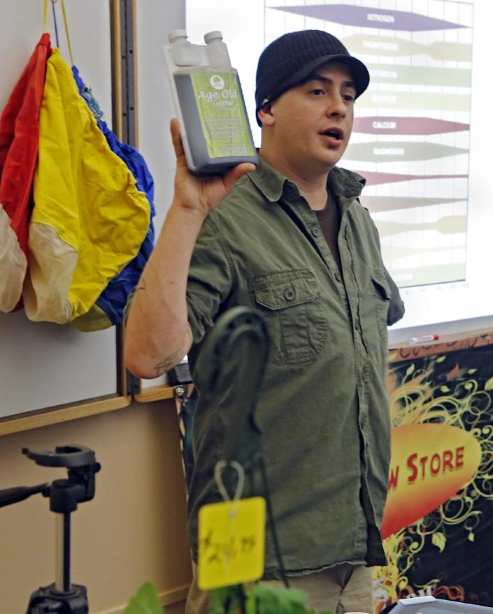 """In this photo taken on Saturday, Feb. 9, 2013, Instructor Ted Smith holds up a chemical that is recommended in growing marijuana during the first class at THC University in Denver. Smith told the first-time marijuana growers that chemical fertilizers work so quickly that some are called """"bud rocket."""" (AP Photo/Ed Andrieski)"""