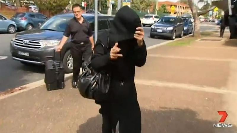 Deborah Levy can be seen covering her face with a black coat after she was an hour late to court. Photo: 7 News