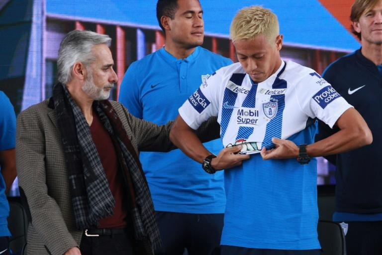 Pachuca's new footballer, Japanese Keisuke Honda, puts his new jersey on next to the team's president Jesus Martinez, during his official presentation, at the Football University on the outskirts of Pachuca, Hidalgo State, Mexico, on July 18, 2017