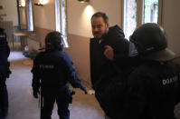 Rap singer Pablo Hasél is detained by police officers at the University of Lleida, Spain, Tuesday, Feb. 16, 2021. A rapper in Spain and dozens of his supporters have locked themselves inside a university building in the artist's latest attempt to avoid a prison sentence for insulting the monarchy and praising terrorism. (AP Photo/Joan Mateu)