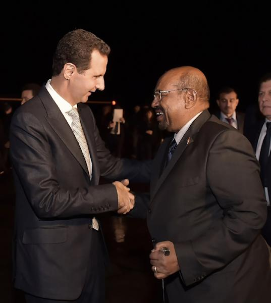 A handout picture released by the official Syrian Arab News Agency (SANA) on December 16, 2018, shows Syrian President Bashar al-Assad (L) welcoming his Sudanese counterpart Omar al-Bashir to Damascus (AFP Photo/STRINGER)