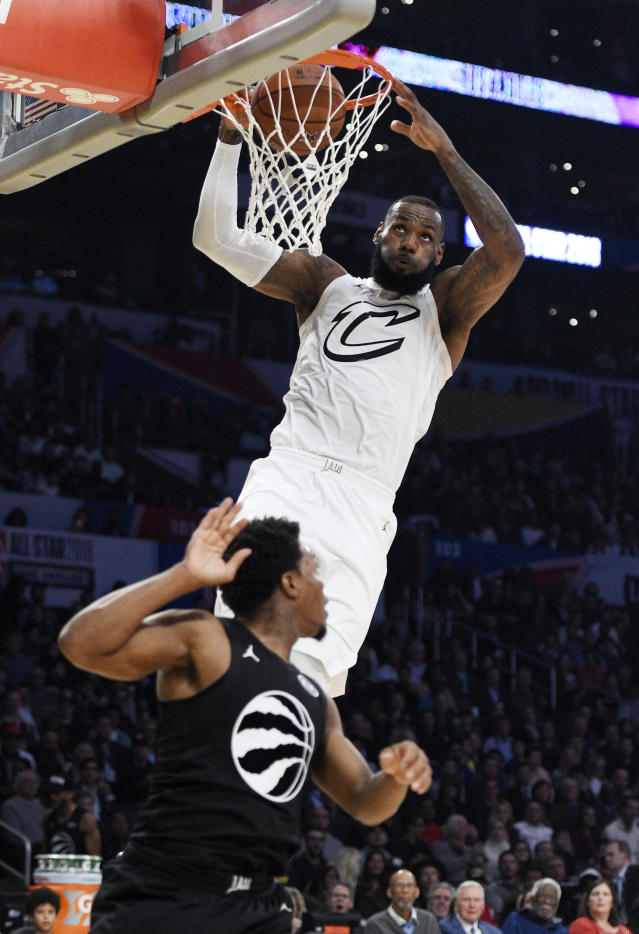 Team LeBron's LeBron James, top, of the Cleveland Cavaliers, dunks over Team Stephen's Kyle Lowry, of the Toronto Raptors, defends during the first half of an NBA All-Star basketball game, Sunday, Feb. 18, 2018, in Los Angeles. (AP Photo/Chris Pizzello)