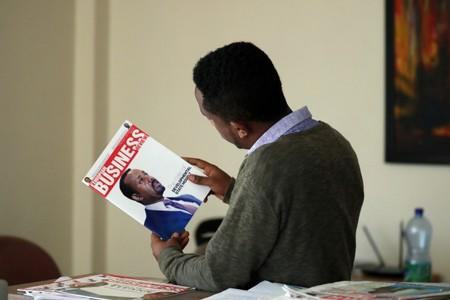 Eritrean refugee Berhane reads news magazine with cover photo of Ethiopian PM at his office in Addis Ababa