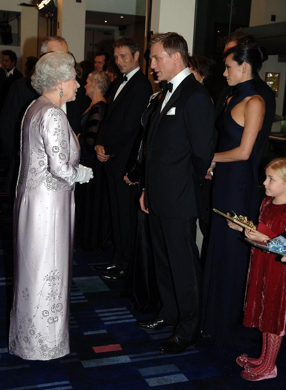 <p>We wonder if Queen Elizabeth is as charmed by Daniel Craig in a sharp tuxedo as we are? Judging by the look of their interaction here, we'd say yes.</p>