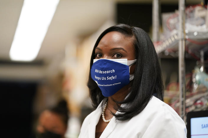 FILE - In this Feb. 11, 2021, file photo, Kizzmekia Corbett, an immunologist with the Vaccine Research Center at the National Institutes of Health (NIH) looks on as President Joe Biden visits the Viral Pathogenesis Laboratory at the NIH in Bethesda, Md. Corbett played a key role in developing the Moderna vaccine. (AP Photo/Evan Vucci, File)