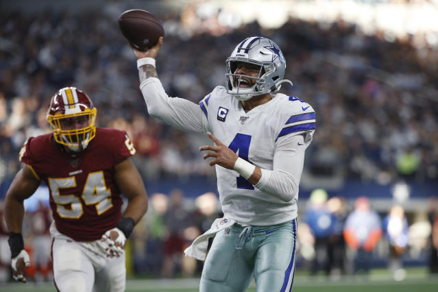 Dallas Cowboys quarterback Dak Prescott (4) delivers a touchdown pass to running back Ezekiel Elliott during the first half of an NFL football game against the Washington Redskins in Arlington, Texas, Sunday, Dec. 15, 2019. (AP Photo/Ron Jenkins)
