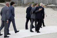 FILE - In this June 11, 2021 file photo, French President Emmanuel Macron, center right, and U.S. President Joe Biden, second right, speaks as they walk on the boardwalk during arrivals for the G7 meeting at the Carbis Bay Hotel in Carbis Bay, St. Ives, Cornwall, England. When U.S. President Joe Biden took office early this year, Western allies were falling over themselves to welcome and praise him and hail a new era in trans-Atlantic cooperation. The collapse of Kabul certainly put a stop to that. Even some of his biggest fans are now churning out criticism. (Phil Noble, Pool via AP, File)