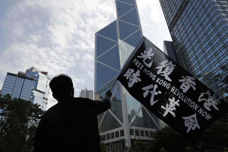 A pro-democracy supporter waves a flag during a rally by the advertising industry in Hong Kong on Monday, Dec. 2, 2019. Thousands of people took to Hong Kong's streets Sunday in a new wave of pro-democracy protests, but police fired tear gas after some demonstrators hurled bricks and smoke bombs, breaking a rare pause in violence that has persisted during the six-month-long movement. (AP Photo/Vincent Thian)