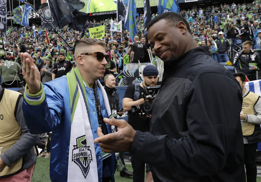 Macklemore, a minority owner of the Seattle Sounders, left, speaks with Ken Griffey Jr., Sunday, Nov. 10, 2019, before the MLS Cup championship soccer match against the Toronto FC in Seattle. (AP Photo/Ted S. Warren)