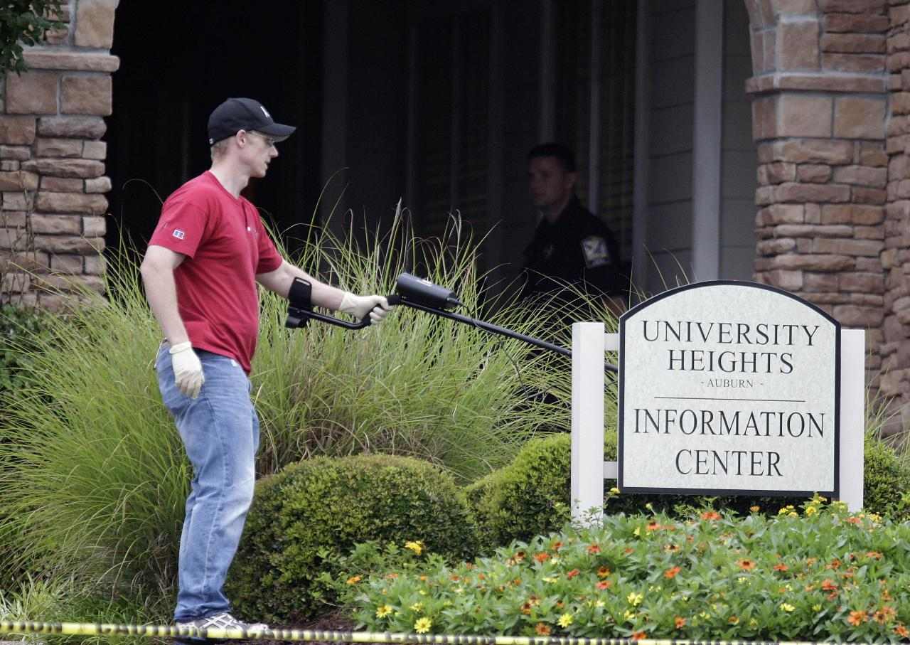 An investigator uses a metal detector to search for evidence at the scene of an overnight shooting at an apartment complex Sunday, June 10, 2012, in Auburn, Ala. Auburn Police Chief Tommy Dawson said authorities responded during the night to a report of multiple gunshot victims at the apartment complex, but he released no immediate information early Sunday. (AP Photo/David Goldman)