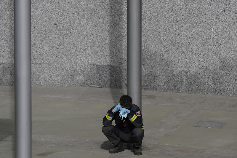 CAPTION CORRECTS THE DATE - In this photo taken on Thursday, April 2, 2020, a firefighter talks on his phone as he rests at a temporary field hospital set in Ifema convention and exhibition in Madrid, Spain. Most of the 1,850 patients brought to the Ifema field hospital are not in serious conditions. In fact, 800 had been discharged by Thursday, although six had died since doors opened 12 days ago. The new coronavirus causes mild or moderate symptoms for most people, but for some, especially older adults and people with existing health problems, it can cause more severe illness or death. (AP Photo/Manu Fernandez)