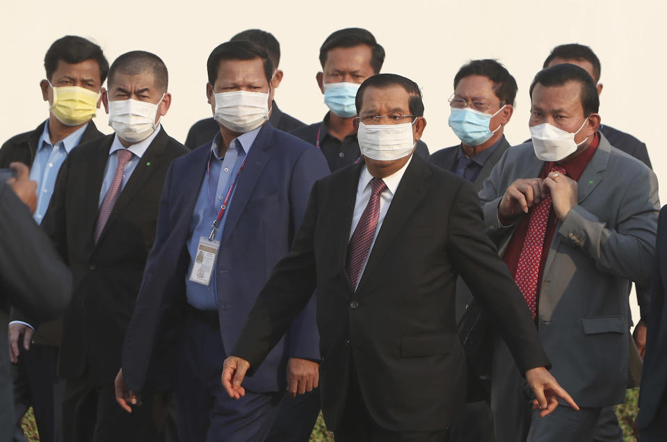 "Cambodian Prime Minister Hun Sen, third right, arrives for a handing over ceremony at Phnom Penh International Airport, in Phnom Penh, Cambodia, Sunday, Feb. 7, 2021. Cambodia on Sunday received its first shipment of COVID-19 vaccine, a donation of 600,000 doses from China, the country's biggest ally. Beijing has been making such donations to several Southeast Asian and African nations in what has been dubbed ""vaccine diplomacy,"" aimed especially at poorer countries like Cambodia. (AP Photo/Heng Sinith)"