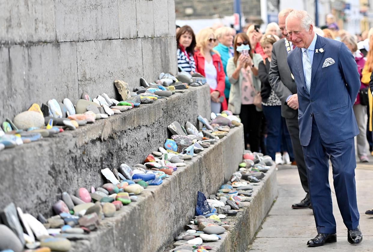 BANGOR, NORTHERN IRELAND - MAY 19: Prince Charles, Prince of Wales views stones which line the Donaghadee Harbour walls and were decorated with messages of hope by local people during the pandemic on May 19, 2021 in Bangor, Northern Ireland. (Photo by Samir Hussein - Pool/WireImage)