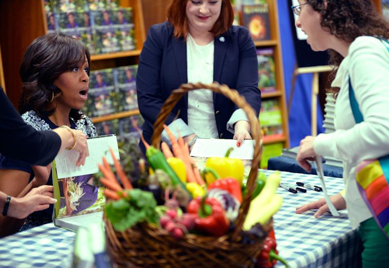 US First Lady Michelle Obama (L) signs a copy of her book 'American Grown: The Story of the White House Kitchen Garden and Gardens Across America,' during a book signing event at Politics & Prose in Washington, DC, on May 7, 2013. Photo credit: JEWEL SAMAD/AFP/Getty Images