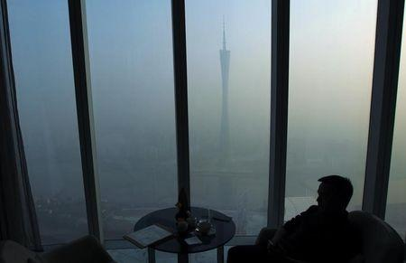 A man sits next to a window of a restaurant on the 70th floor of a skyscraper as the Guangzhou TV Tower is seen through thick hazy at the central business district in Guangzhou, Guangdong province February 17, 2014. REUTERS/Alex Lee/Files