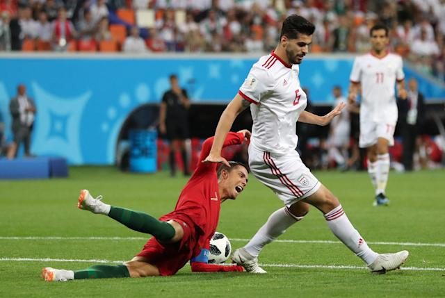 Soccer Football - World Cup - Group B - Iran vs Portugal - Mordovia Arena, Saransk, Russia - June 25, 2018 Iran's Saeid Ezatolahi fouls Portugal's Cristiano Ronaldo for a penalty REUTERS/Ivan Alvarado