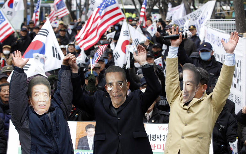 South Korean activists wearing masks of U.S. President Barack Obama, center, South Korean President Lee Myung-bak, right, and former late President Roh Moo-hyun, cheer to celebrate the free trade agreement, or FTA, with the United States during a rally near the U.S. Embassy in Seoul, South Korea, Wednesday, March 14, 2012. South Korea is implementing its long-stalled free trade deal with the United States about five years after the two countries struck the accord. South Korean trade officials say the pact aimed at slashing tariffs and other trade barriers is to take effect at midnight Wednesday. (AP Photo/Lee Jin-man)