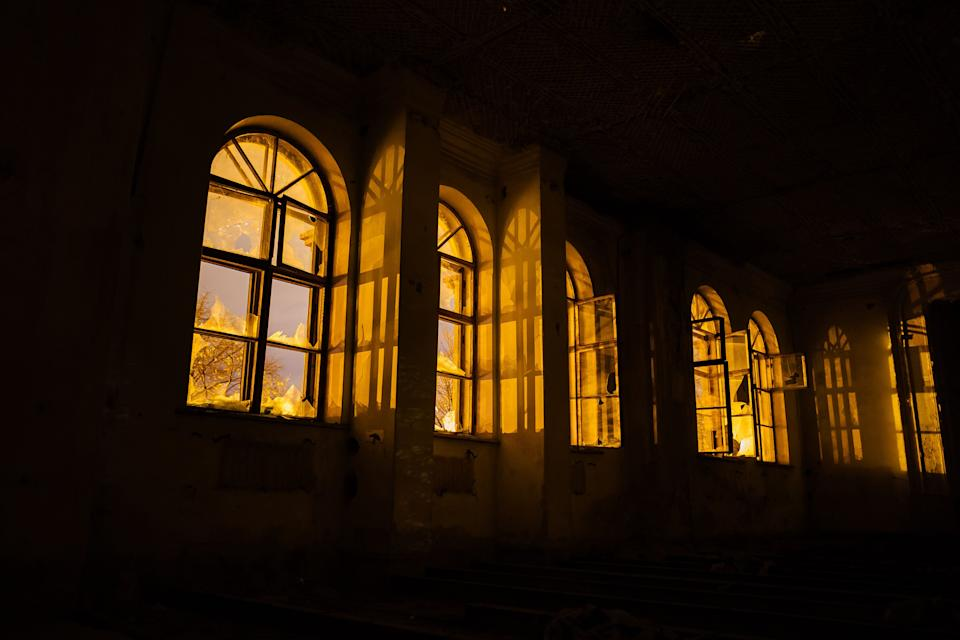 Broken windows of old ruined abandoned mansion at night. (Photo: Vladimir Zapletin via Getty Images)