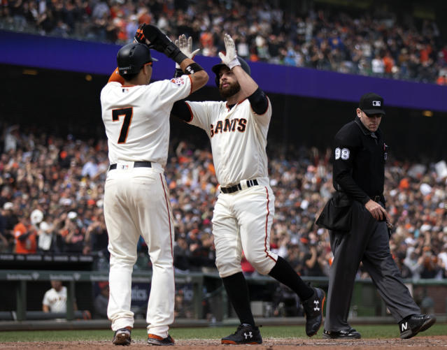 San Francisco Giants right fielder Gorkys Hernandez, left, congratulates Brandon Belt, right, on his three-run home run against the Colorado Rockies during the seventh inning of a Major League Baseball game, Sunday, May 20, 2018, in San Francisco. Evan Longoria also scored. Umpire is Chris Conroy. (AP Photo/D. Ross Cameron)