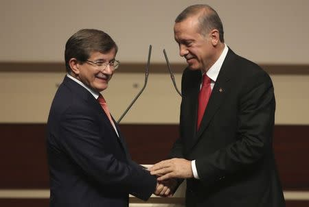 Turkey's PM Erdogan shakes hands with Foreign Minister Davutoglu during a meeting at the AK Party headquarters in Ankara
