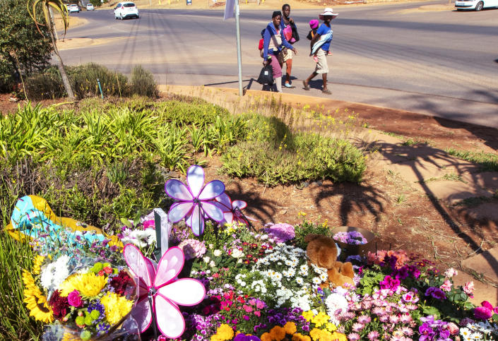 Pedestrians walk past flowers outside the complex where the Dickason family lived prior to their emigration to New Zealand, in Pretoria, South Africa, Thursday, Sept. 23, 2021. People in the town of Timaru are planning an evening vigil outside the home of three young girls who were killed last week in a crime that shocked New Zealand. The girls' mother Lauren Dickason has been charged with their murder. (AP Photo/Themba Hadebe)