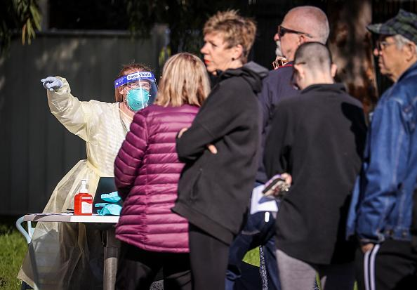 A worker wearing a face mask and protective clothing attends to members of the public at a pop-up COVID-19 testing clinic in the town of Albury, Australia.