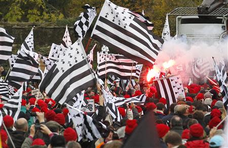 "Protesters wearing red caps, the symbol of protest in Brittany and waving Breton regional flags, take part in a demonstration to maintain jobs in the region and against an ""ecotax"" on commercial trucks, in Carhaix, western France, November 30, 2013. REUTERS/Mal Langsdon"