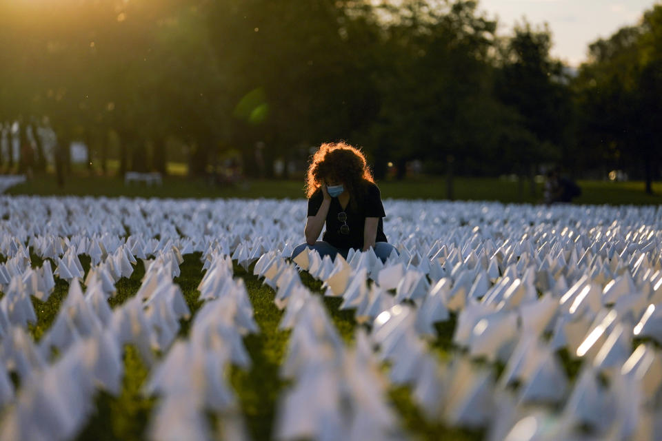 """FILE - In this Sept. 17, 2021, file photo, Zoe Nassimoff, of Argentina, looks at white flags that are part of artist Suzanne Brennan Firstenberg's temporary art installation, """"In America: Remember,"""" in remembrance of Americans who have died of COVID-19, on the National Mall in Washington. Nassimoff's grandparent who lived in Florida died from COVID-19. (AP Photo/Brynn Anderson, File)"""