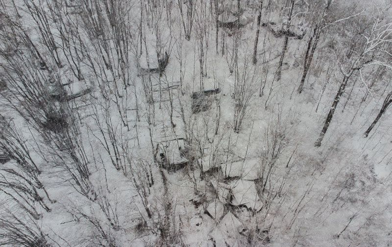 Tents in makeshift camp are seen during snowfall in a forest near Velika Kladusa