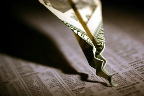 A paper airplane made out of a dollar bill that's crashed onto the financial section of a newspaper.