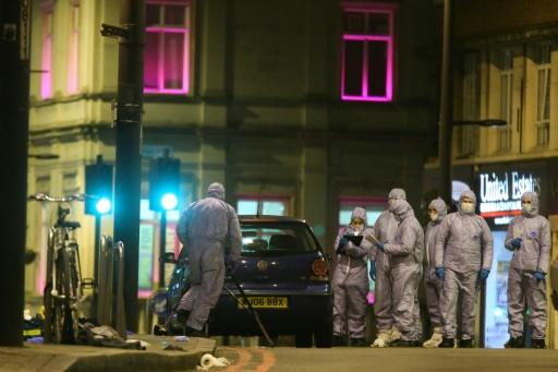 Police forensic officers work on Streatham High Road in south London after Sudesh Amman, 20, who was wearing a fake suicide vest, was shot on the busy road packed with shoppers
