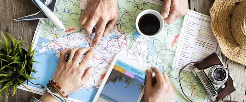 Two people planning to travel over a map