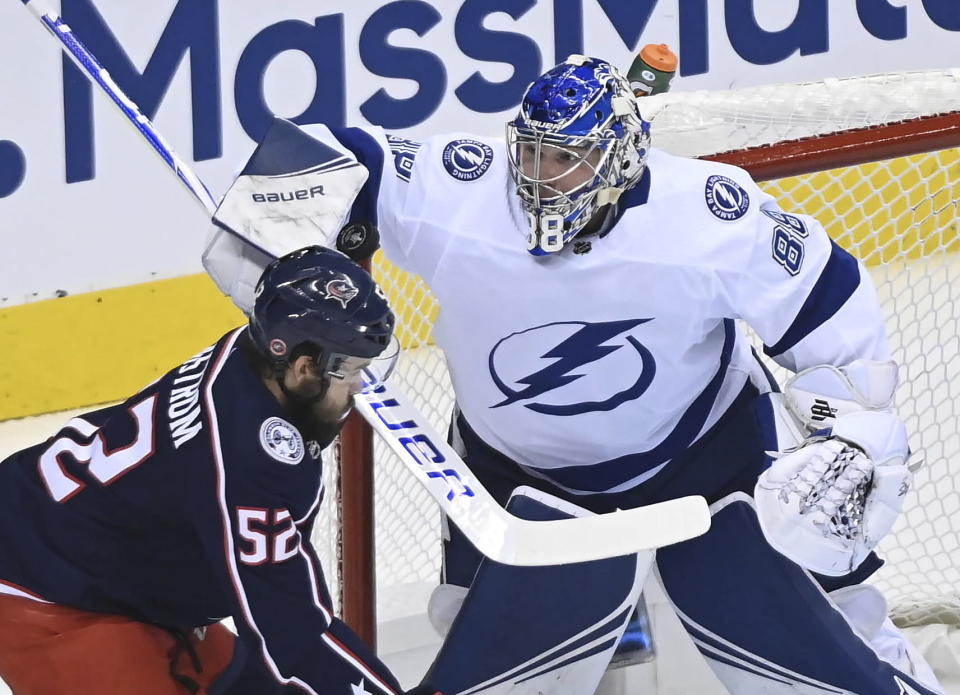 Tampa Bay Lightning goaltender Andrei Vasilevskiy (88) makes a save as Columbus Blue Jackets center Emil Bemstrom (52) skates near the net during the first period of Game 3 of an NHL hockey first-round playoff series, Saturday, Aug. 15, 2020, in Toronto. (Nathan Denette/The Canadian Press via AP)