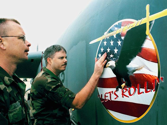 U.S. Air Force Reservists Tech. Sgt. Ron (L) and Staff Sgt. Brian of the 93rd Bomber Squadron apply a decal with the phrase