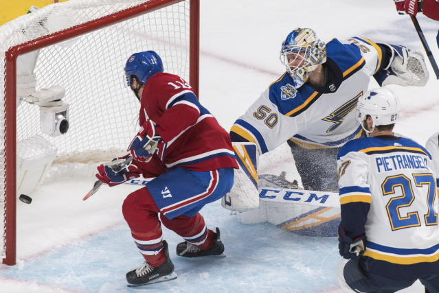 St. Louis Blues goaltender Jordan Binnington is scored on by Montreal Canadiens' Tomas Tatar, not shown, as Canadiens' Brendan Gallagher (11) and Blues' Alex Pietrangelo look for a rebound during first period NHL hockey action in Montreal, Saturday, Oct. 12, 2019. (Graham Hughes/The Canadian Press via AP)