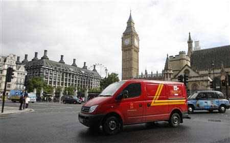 A Royal Mail passes the Houses of Parliament behind it, in central London, September 12, 2013. REUTERS/Eddie Keogh