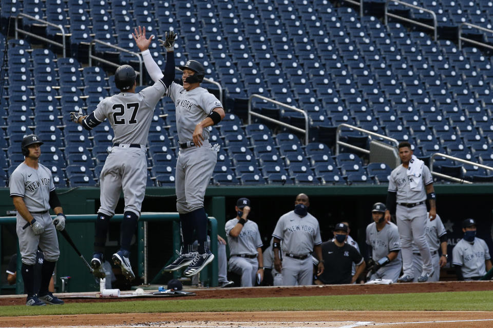 New York Yankees' Giancarlo Stanton (27) jumps to celebrate his two-run homer with Aaron Judge during the first inning of an opening day baseball game against the Washington Nationals at Nationals Park, Thursday, July 23, 2020, in Washington. (AP Photo/Alex Brandon)
