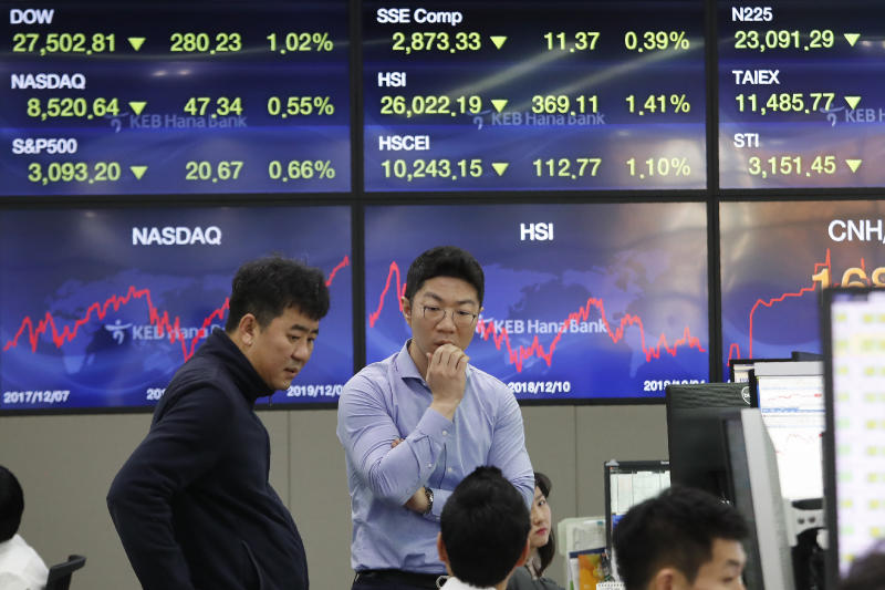 Currency traders work at the foreign exchange dealing room of the KEB Hana Bank headquarters in Seoul, South Korea, Wednesday, Dec. 4, 2019. Asian stock markets followed Wall Street lower after President Donald Trump cast doubt over the potential for a trade deal with China this year. (AP Photo/Ahn Young-joon)