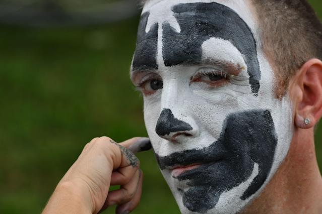 <p>A fan of the rap group Insane Clown Posse, known as Juggalos, gets his face painted as several thousand fans prepare to assemble on Sept. 16, 2017 near the Lincoln Memorial in Washington to protest at a 2011 FBI decision to classify their movement as a gang. (Photo: Paul J. Richards/AFP/Getty Images) </p>