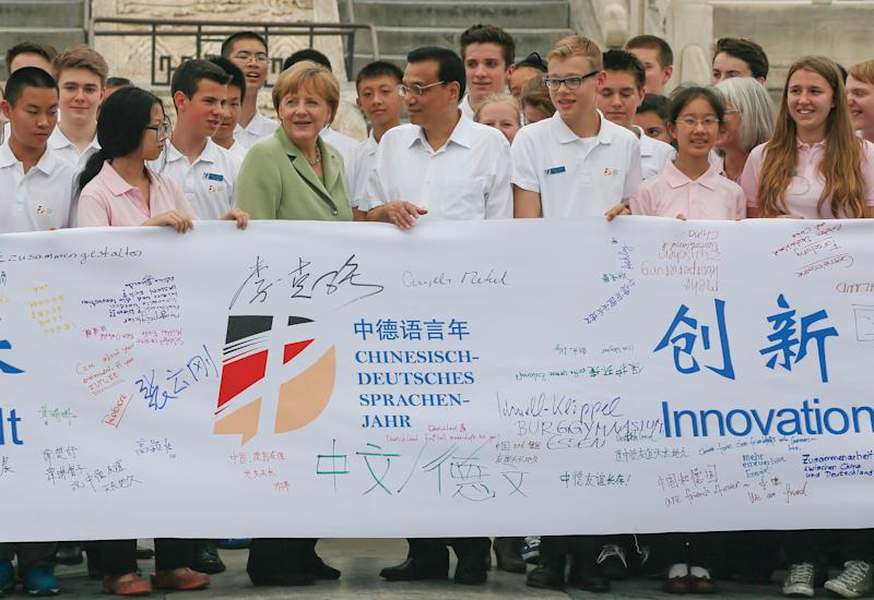 Angela Merkel (4th left) and Chinese Premier Li Keqiang (5th left) join Chinese and German highschool students holding a symbolic banner during a visit to the Temple of Heaven in Beijing on July 7, 2014 (AFP Photo/Rolex Dela Pena)