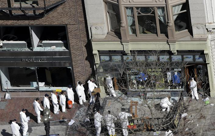 A line of investigators is form as they enter a building adjacent to one of the blast sites near the Boston Marathon finish line, Thursday, April 18, 2013, in Boston. Boston remained under a heavy security presence, with scores of National Guard troops gathering among armored Humvees in the Boston Common. (AP Photo/Julio Cortez)