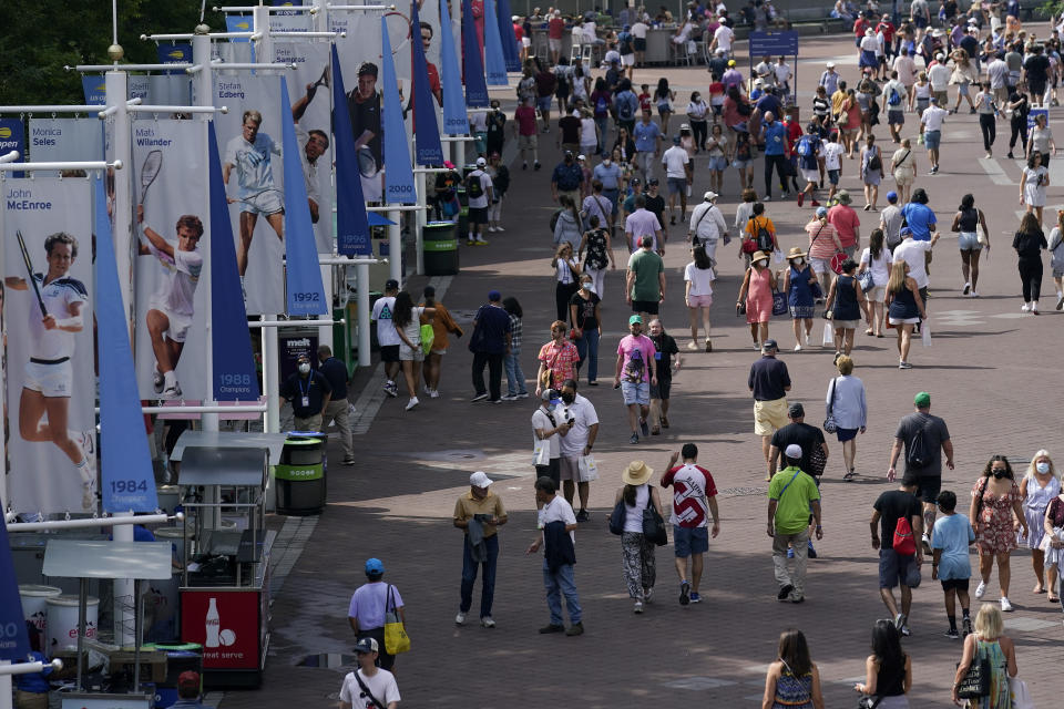 Tennis fans walk the grounds of the Billie Jean King National Tennis Center during the first round of the US Open tennis championships, Monday, Aug. 30, 2021, in New York. (AP Photo/Seth Wenig)