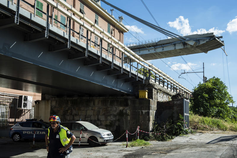 A worker inspecst the the area around the collapsed Morandi highway bridge, in Genoa, northern Italy, Wednesday, Aug. 15, 2018. A bridge on a main highway linking Italy with France collapsed in the Italian port city of Genoa during a sudden, violent storm, sending vehicles plunging 90 meters (nearly 300 feet) into a heap of rubble below. (AP Photo/Nicola Marfisi)