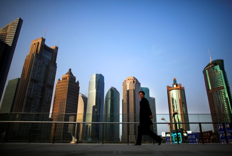 FILE PHOTO: A man walks at the financial district of Pudong in Shanghai