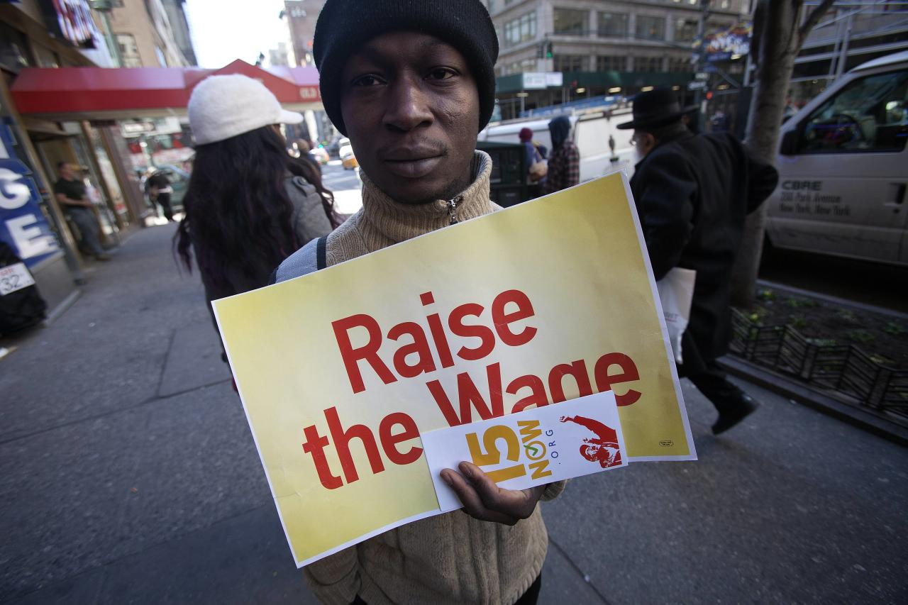 A protester holds a sign outside a McDonald's outlet, as they demand higher wages for fast food workers in the Manhattan borough of New York March 18, 2014. REUTERS/Carlo Allegri (UNITED STATES - Tags: CIVIL UNREST SOCIETY)