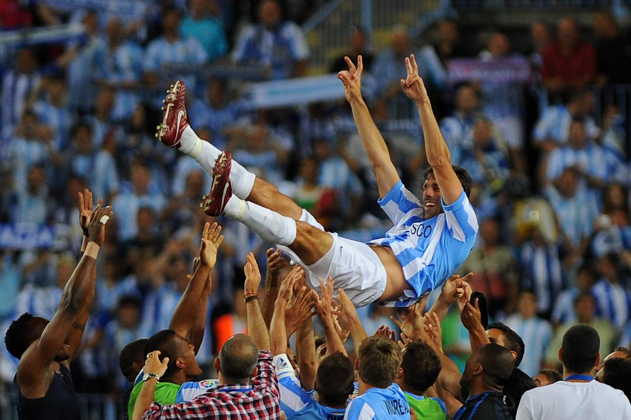 Malaga's Dutch forward Ruud van Nistelrooy is tossed by his teammates during the Spanish league football match Malaga CF vs Sporting Gijon on May 13, 2012 at the Rosaleda stadium in Malaga.    AFP PHOTO/ JORGE GUERRERO