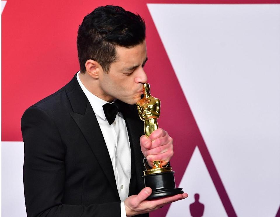 Rami Malek kisses his best actor Oscar for Bohemian Rhapsody, in which he played late Queen frontman Freddie Mercury (Credit: AFP Photo/FREDERIC J. BROWN)