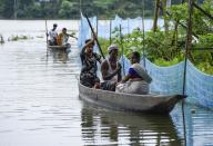 Villagers use a country boat to move across a flooded locality in Kamrup district of Assam, in India on 14 July 2020. (Photo by David Talukdar/NurPhoto via Getty Images)