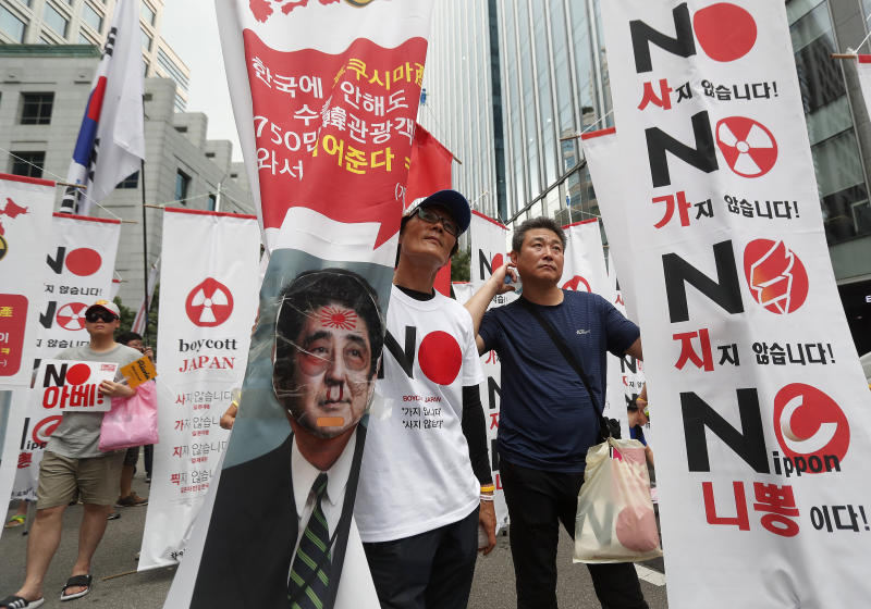 """South Korean protesters hold banners with a defaced image of Japanese Prime Minister Shinzo Abe during a rally to denounce Japan's new trade restrictions on South Korea in front of the Japanese embassy in Seoul, South Korea, Saturday, Aug. 3, 2019. Japan's Cabinet on Friday approved the removal of South Korea from a list of countries with preferential trade status, prompting retaliation from Seoul where a senior official summoned the Japanese ambassador and told him that South Koreans may no longer consider Japan a friendly nation. The signs read: """"We don't buy Japanese products."""" (AP Photo/Ahn Young-joon)"""