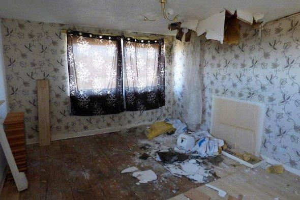 A dilapidated room with the ceiling falling in.
